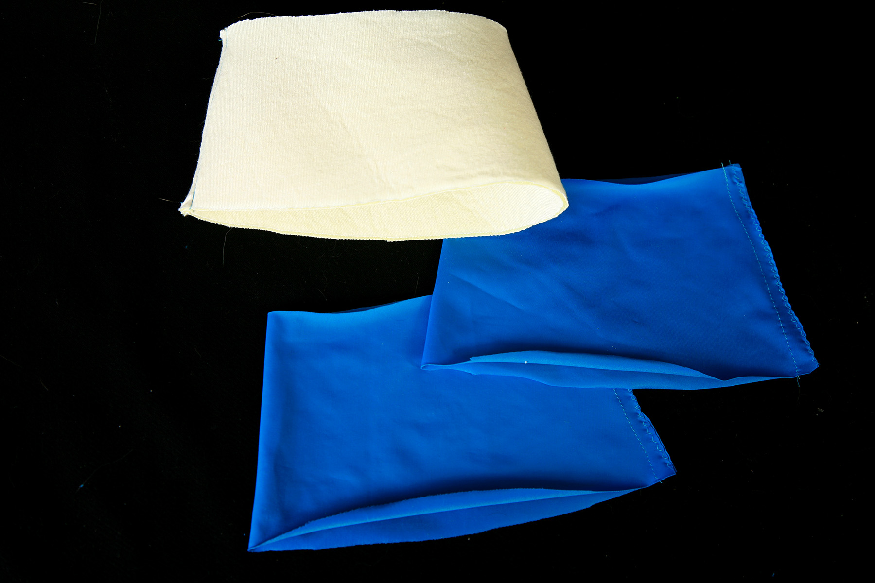 3 cuff pieces - 2 blue spandex pieces, 1 foam piece - laying on a black background.