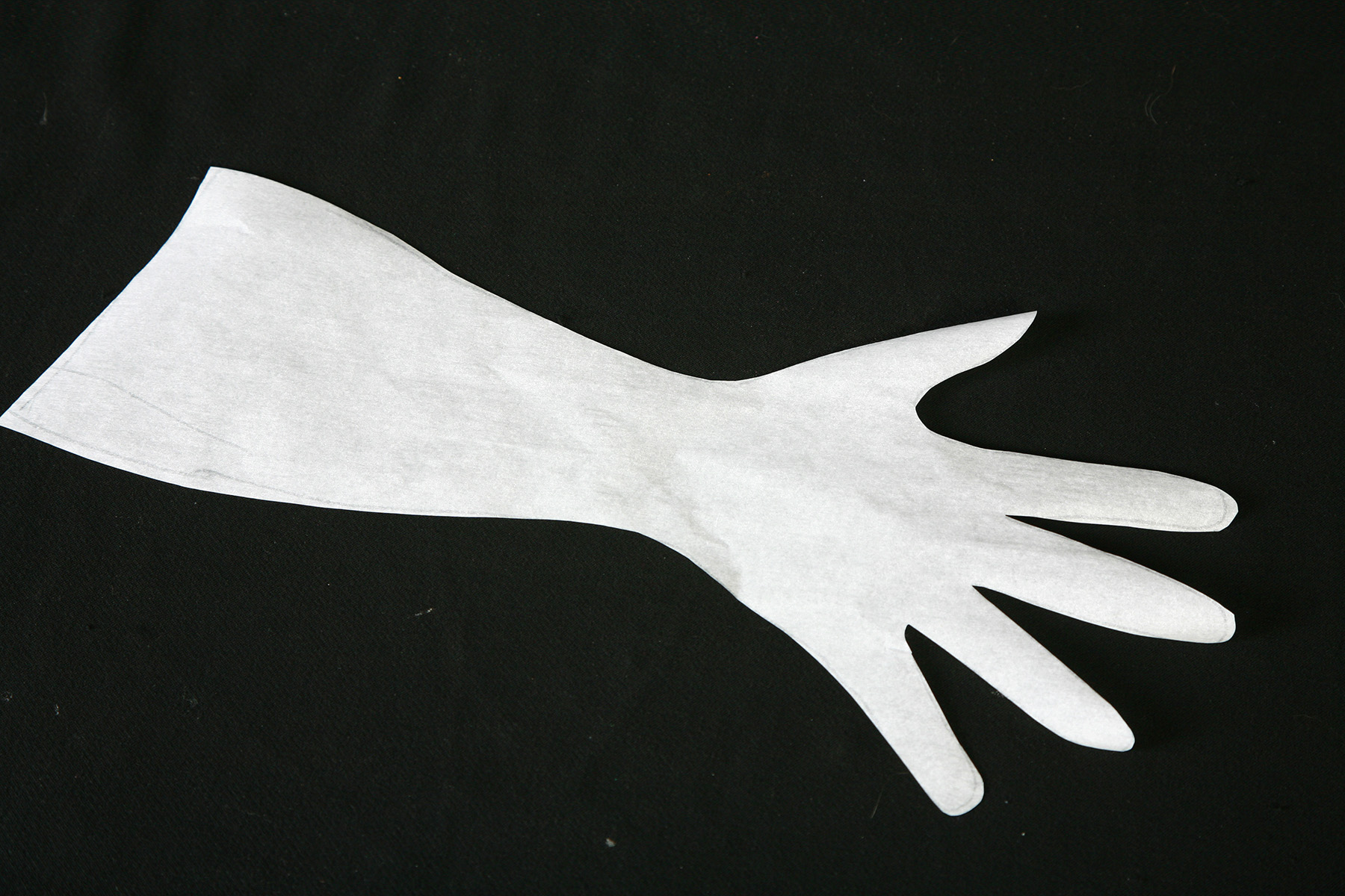 A spandex glove pattern that has been cut out of translucent paper, on a black background.