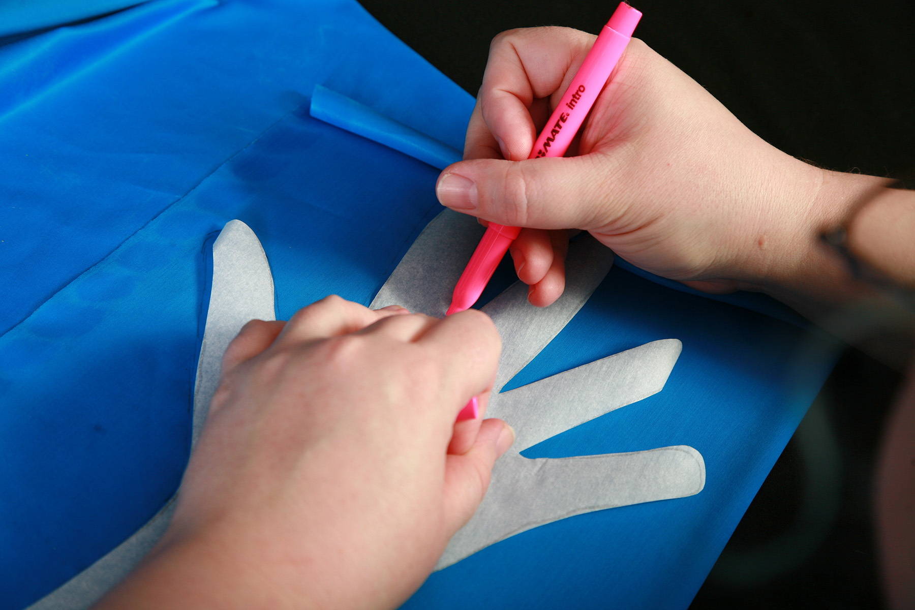 A glove pattern is being traced onto blue spandex fabric.