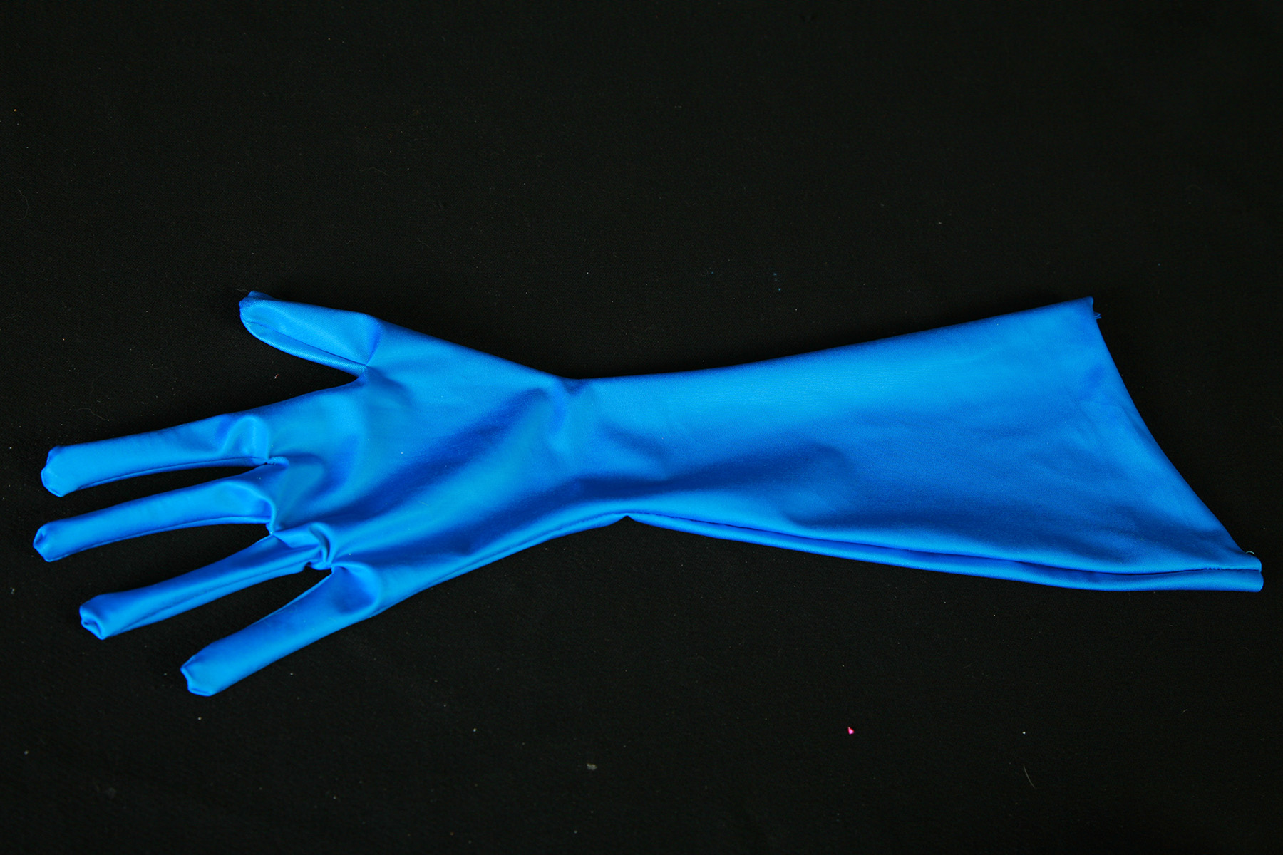 A blue spandex glove against a black background.
