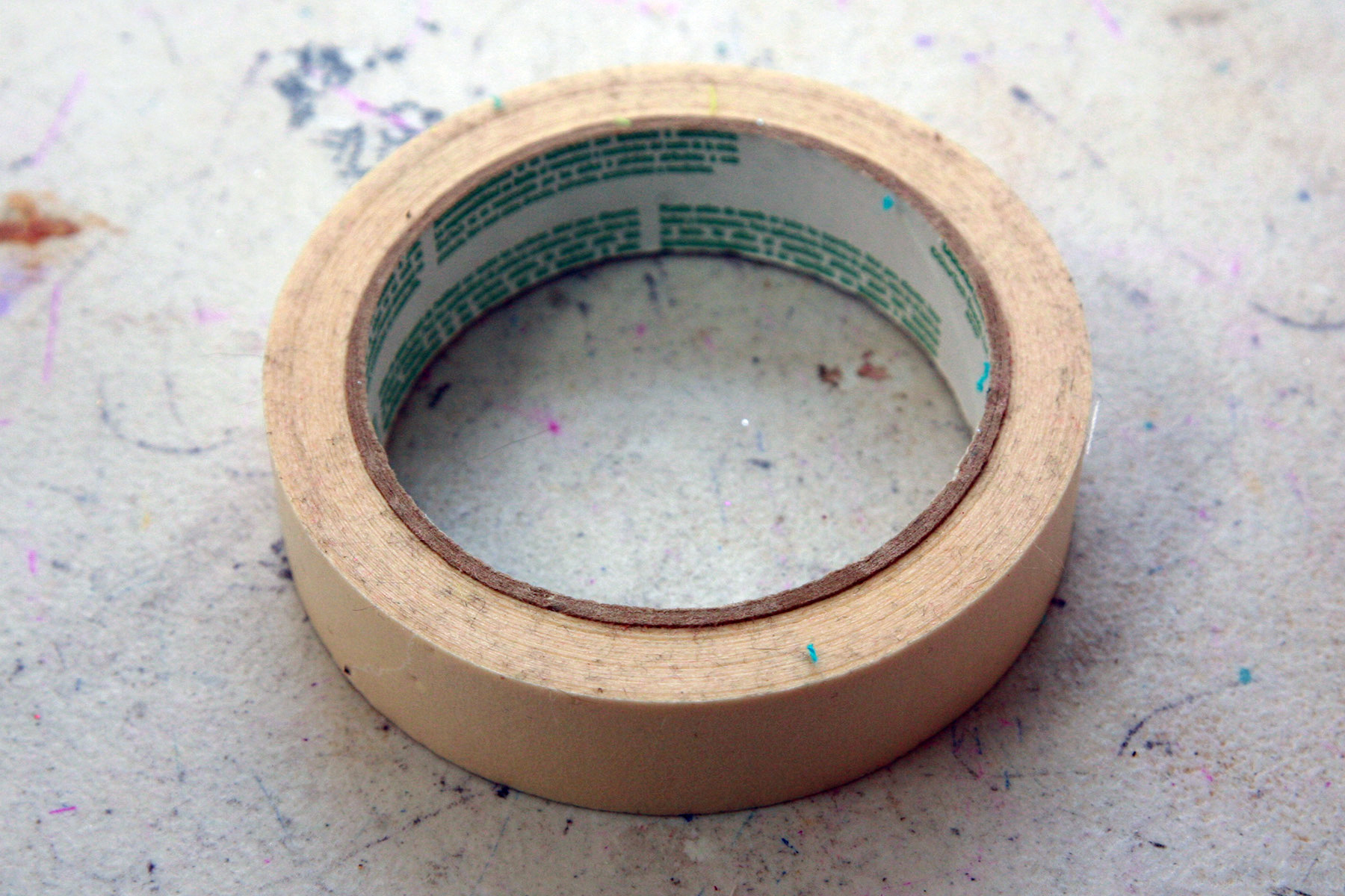 A single roll of masking tape on a work table.