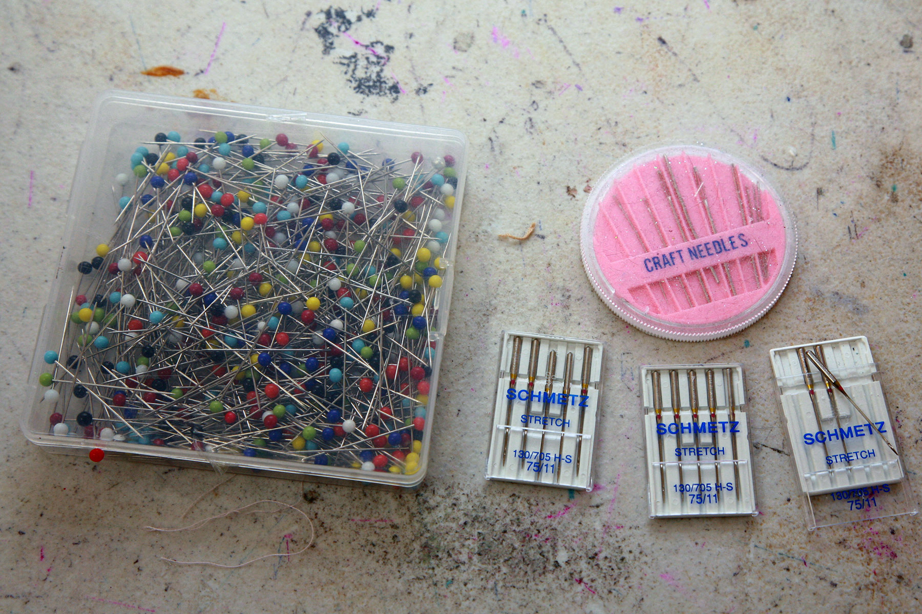 A selection of pins, hand sewing needles, and machine sewing needles.