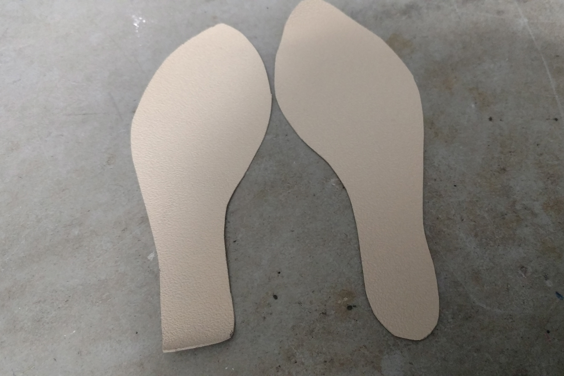 Two shoe-sole shaped pieces of nonslip sole fabric are laid out on a work table.