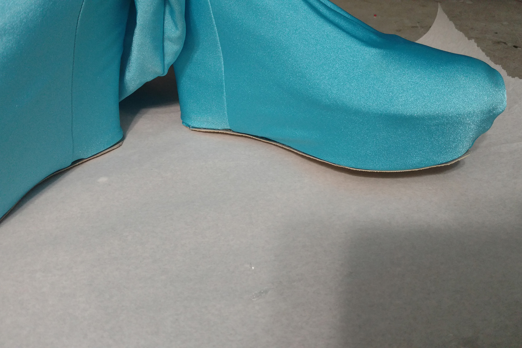Two fabric covered shoes are shown, right side up, on the work surface. They are covered in a bright blue fabric.