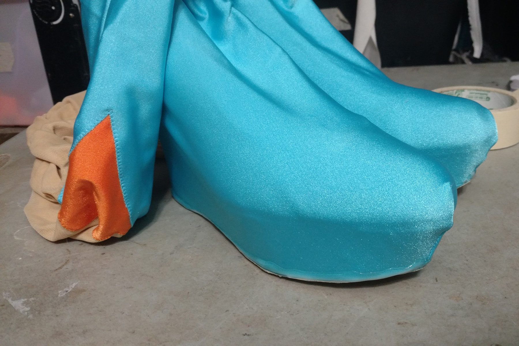 Two high, wedge heeled shoes are covered in bright blue spandex.