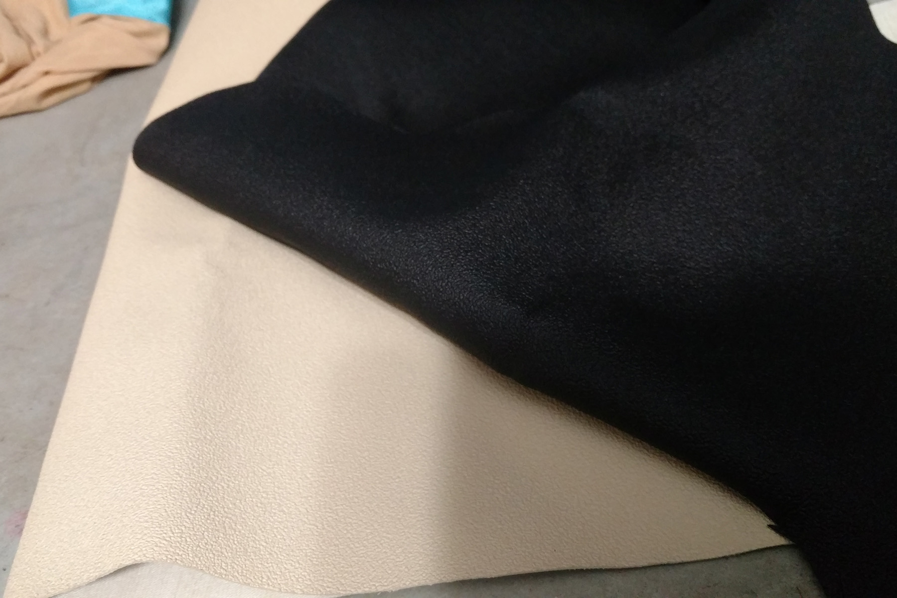 Two pieces of textured fabric are shown. One is beige, the other black.