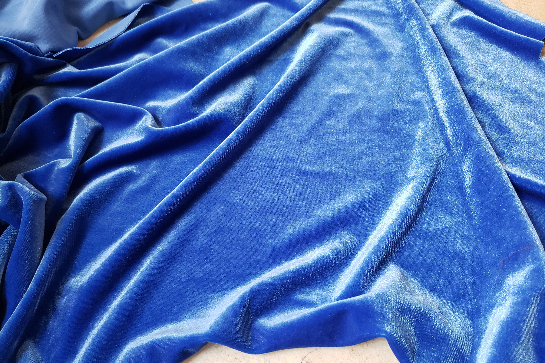 A swath of blue stretch velvet is draped over a work surface.
