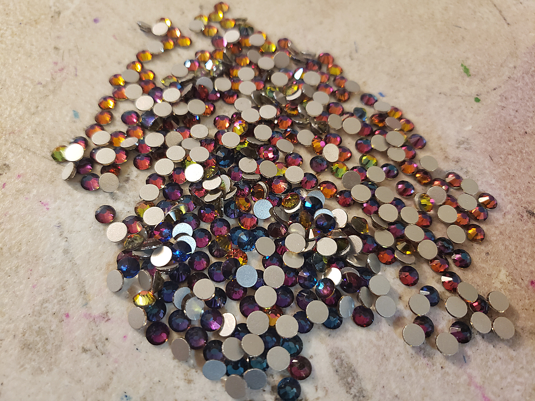 "A small pile of purple ""volcano"" rhinestones. They are purple and blue with pink and orange reflections."