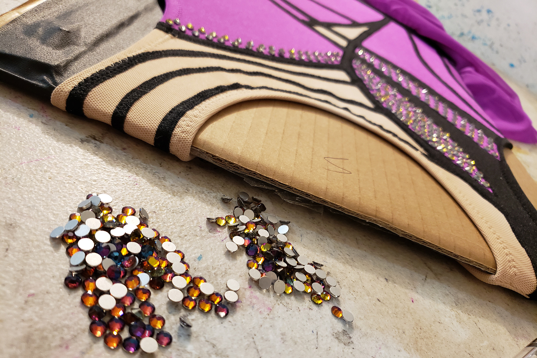 A close up view of the purple and black skating dress on a cardboard stretcher, with a pile of purple-blue rhinestones in front of it.