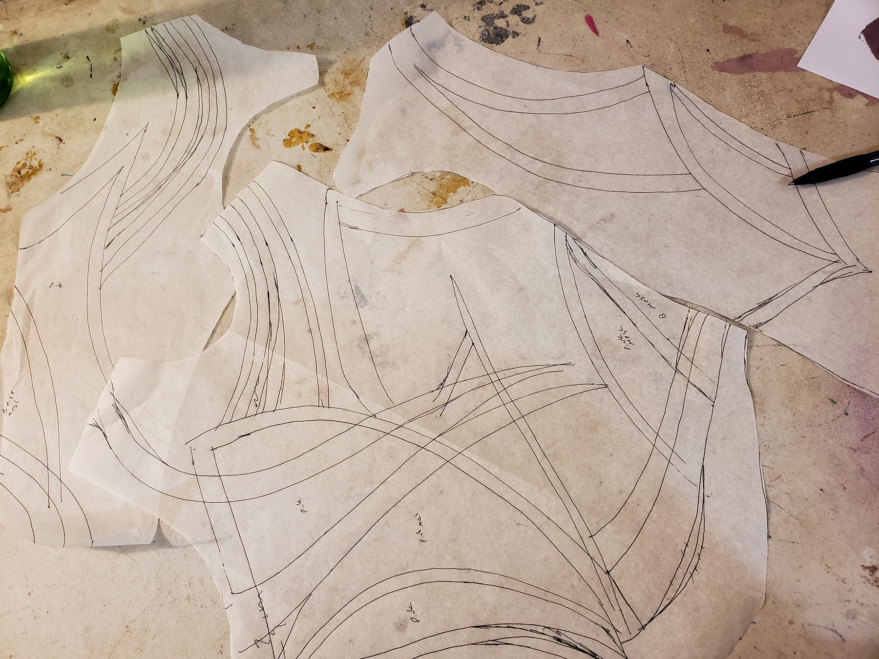 A small pile of bodice pattern pieces on a work table. They are all marked with design lines.