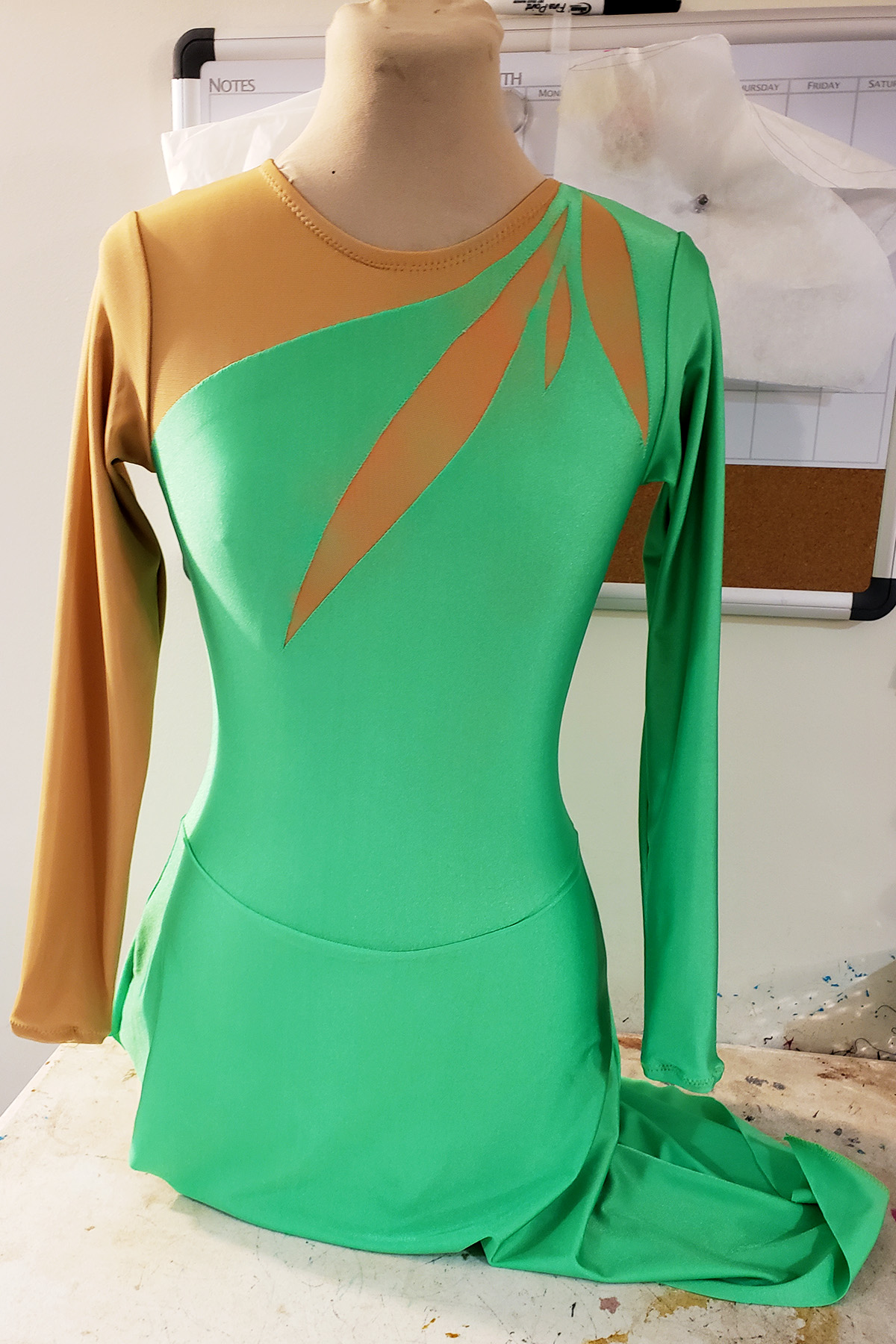 Front view of a basic green figure skating dress on a dress form.
