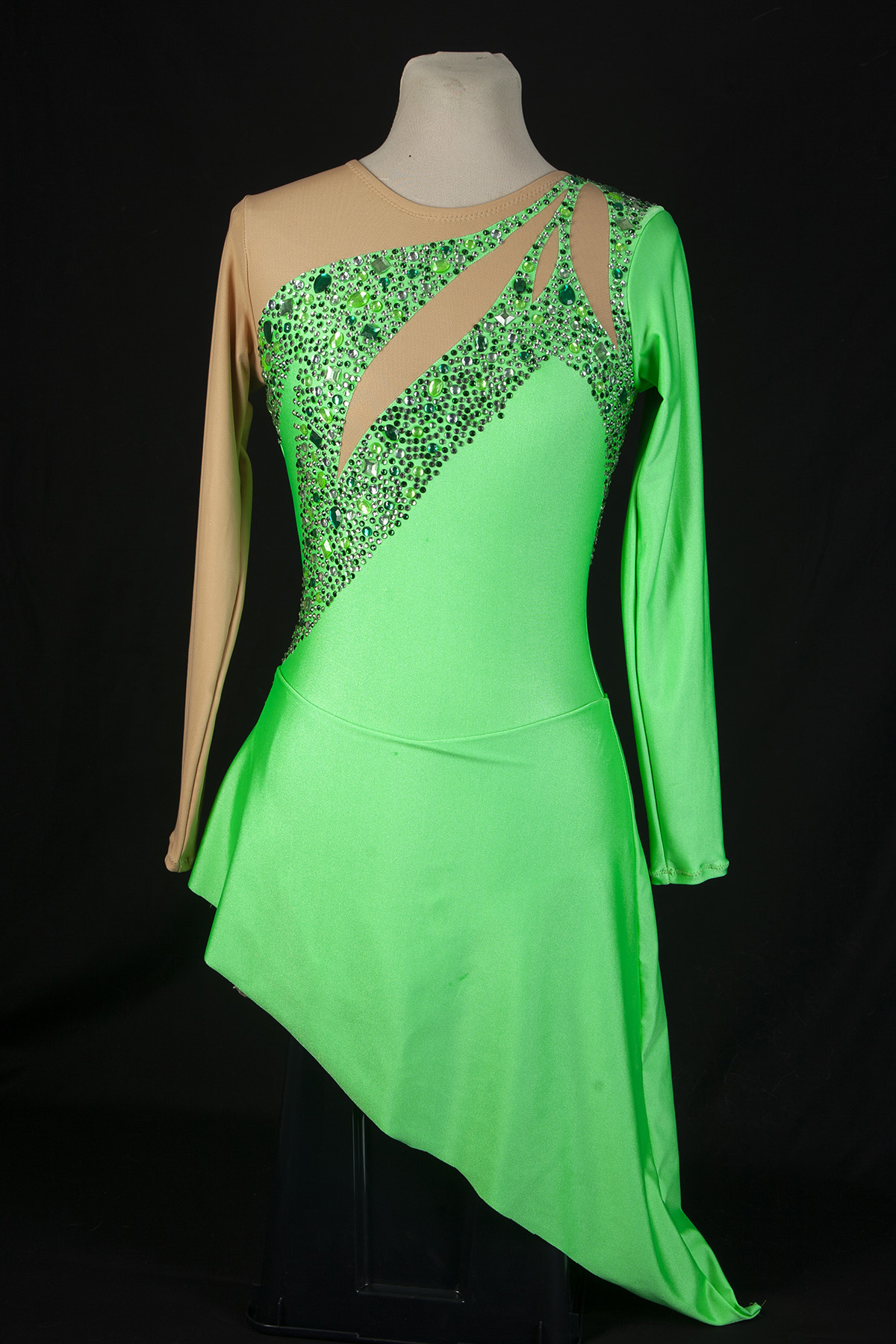 A formal, green figure skating dress, heavily encrusted with clear and green rhinestones.  Front view of the dress, against a black background.