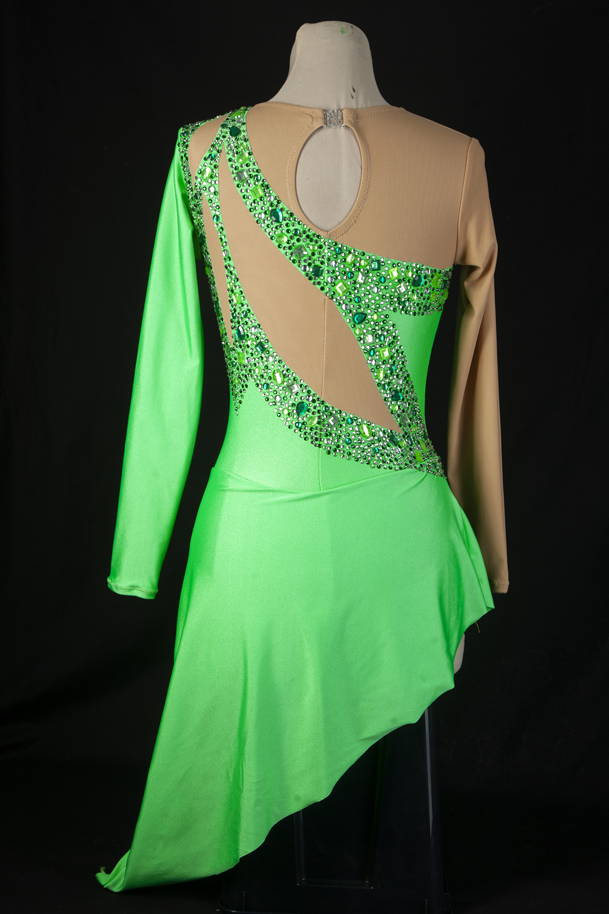 A formal, green figure skating dress, heavily encrusted with clear and green rhinestones.  Back view of the dress, against a black background.