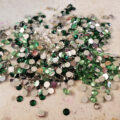 A pile of clear and green rhinestones, on a grey work surface.