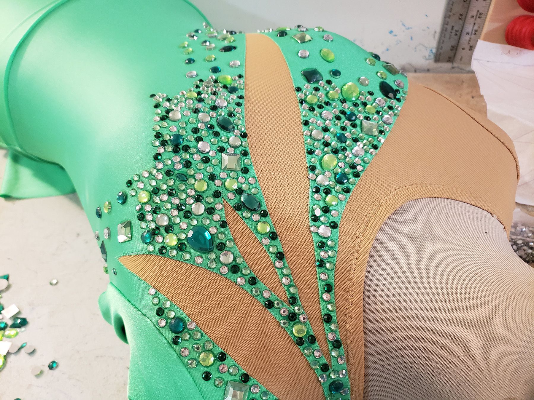 A green skating dress on a dress form, with large rhinestones glued on. The rhinestones are clear and various shades of green, in a variety of shapes and sizes.
