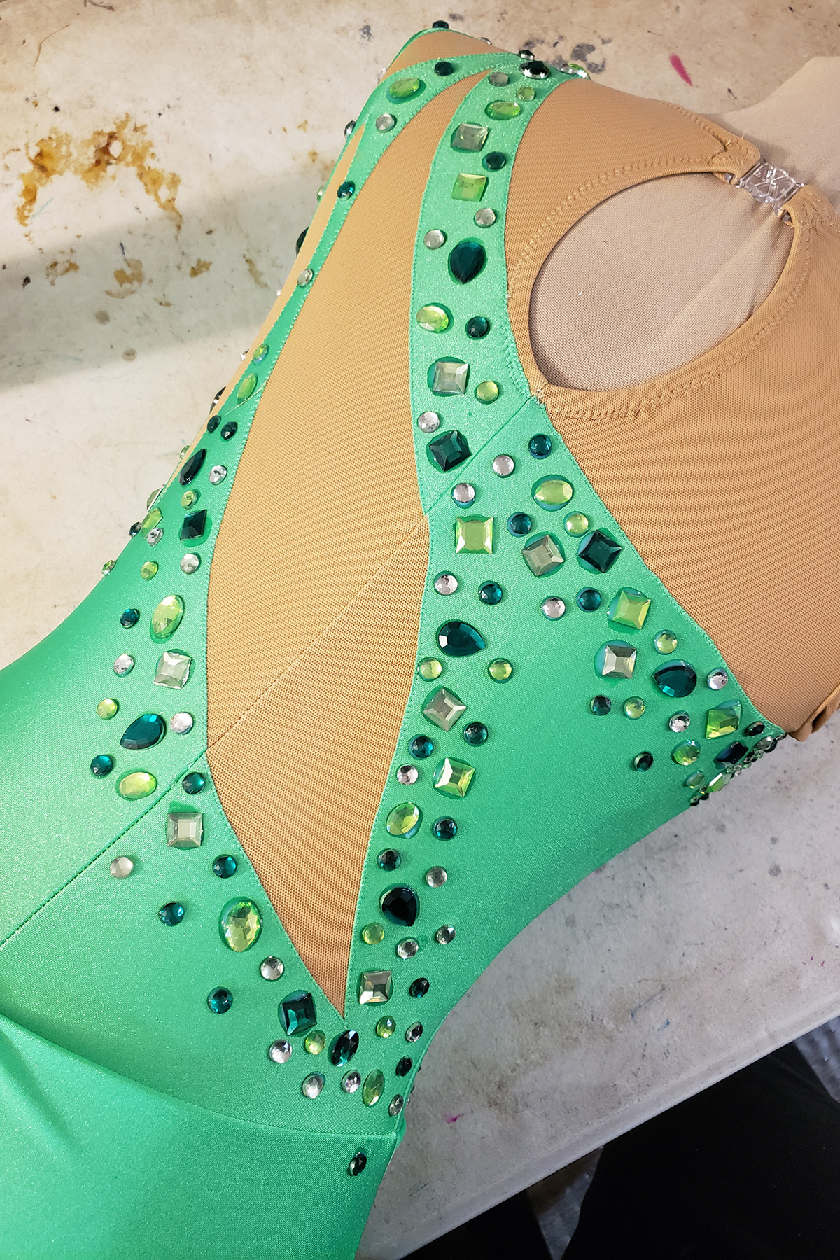 A green skating dress on a dress form, with large rhinestones glued on. The rhinestones are clear and various shades of green, in a variety of shapes.