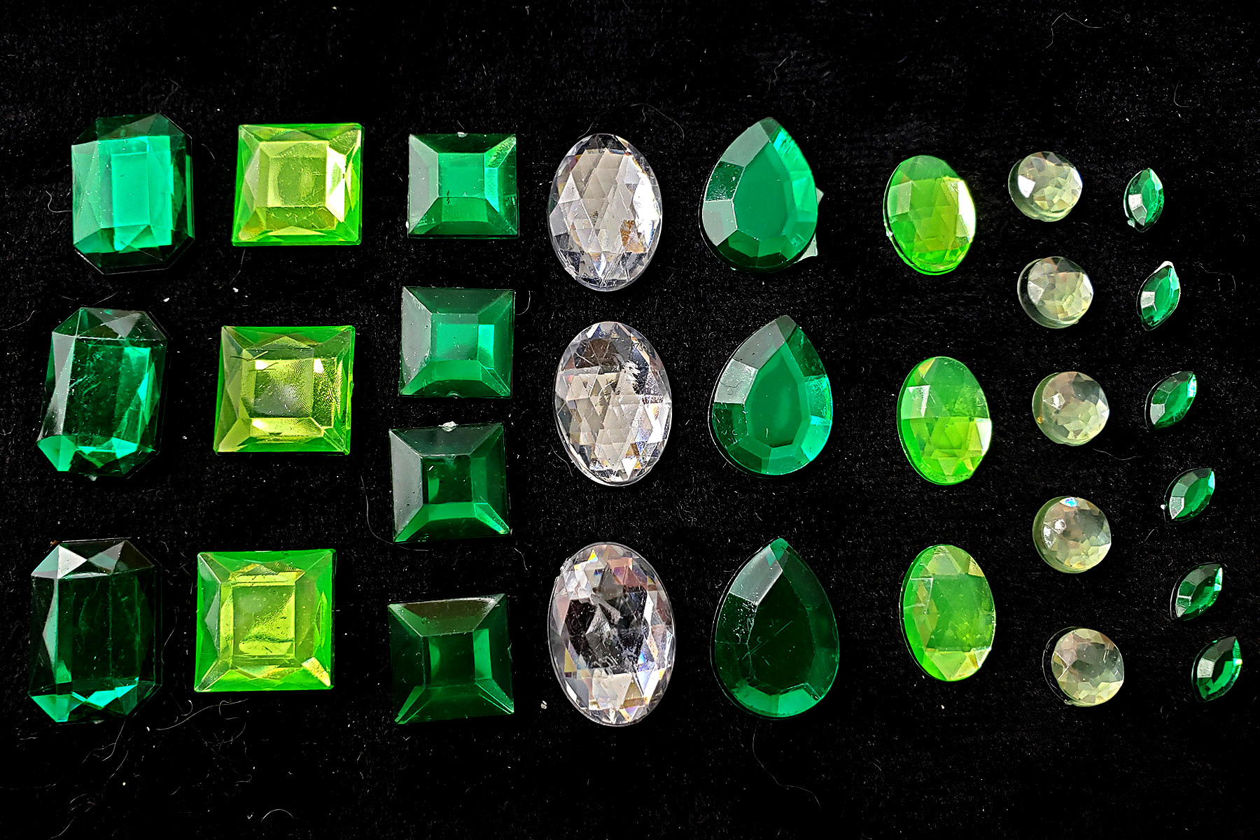 Green and clear rhinestones of various shapes, against a black background.
