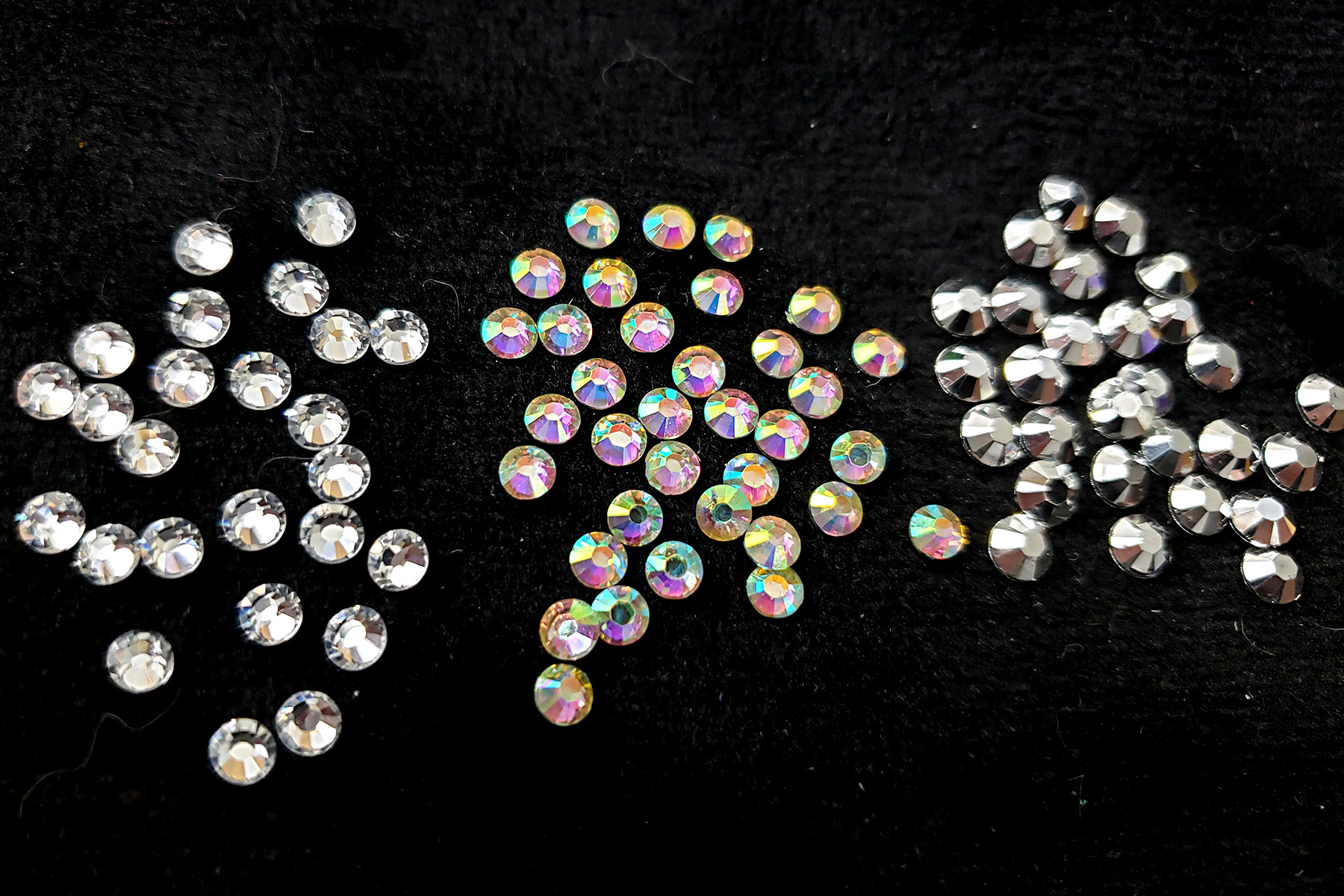 A side by side comparison of clear, AB, and metallic finished rhinestones, against a black background.
