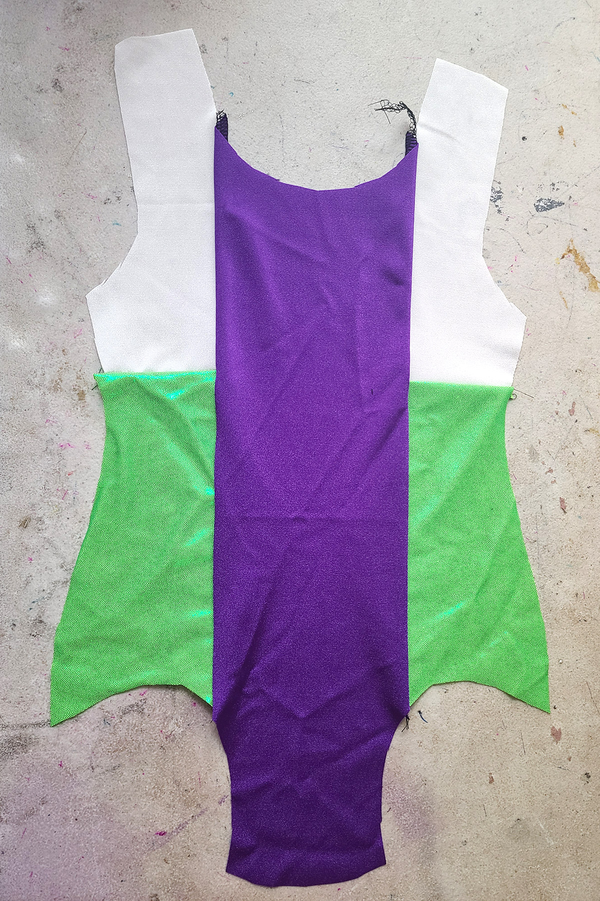 The front of the colour blocked leotard - purple in the middle, with white and green sections to either side.