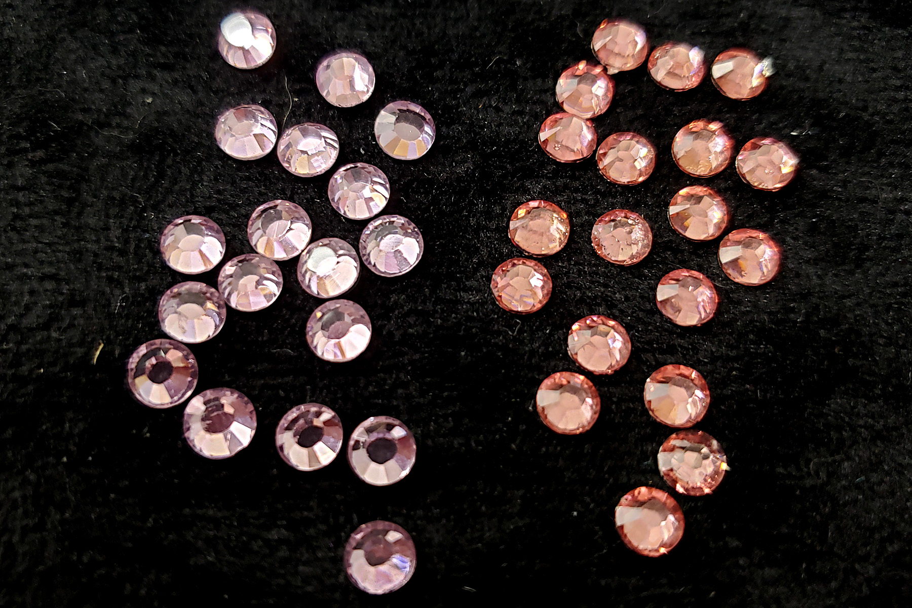 Small piles of two different pink rhinestones, against a black background.