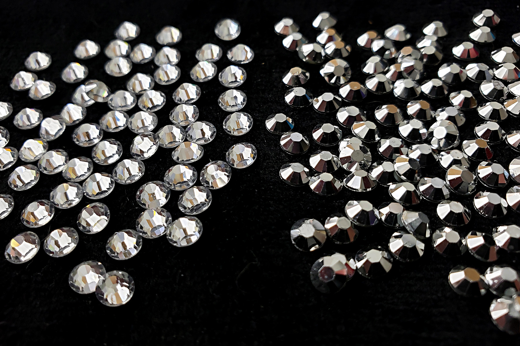 A side by side comparison of clear rhinestones next to silver rhinestones, against a black background.