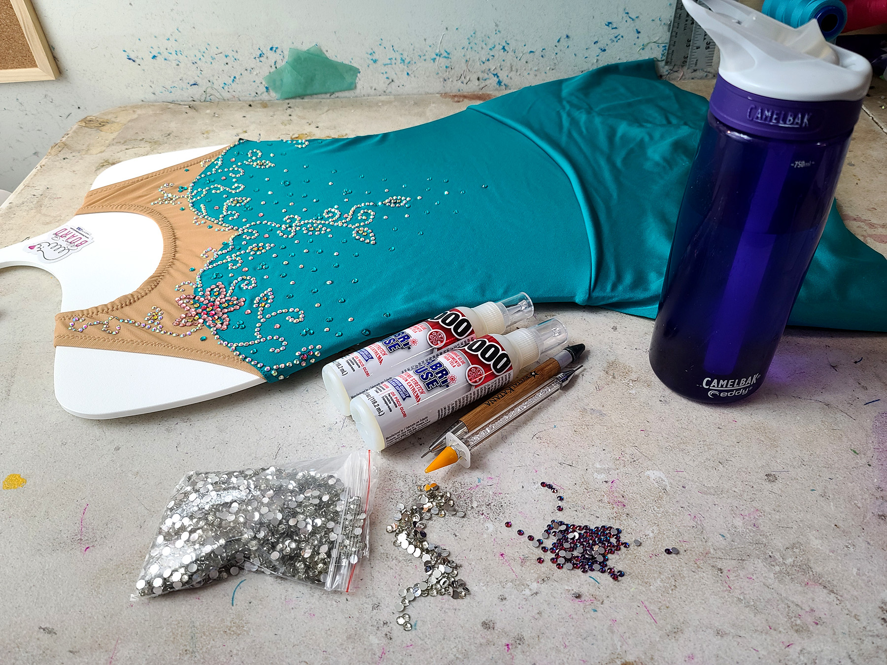 A teal skating dress on a Rhino-Stone board, several bottles of E-6000 Fabri-Fuse, crystals, and a water bottle are groups together on a work surface.