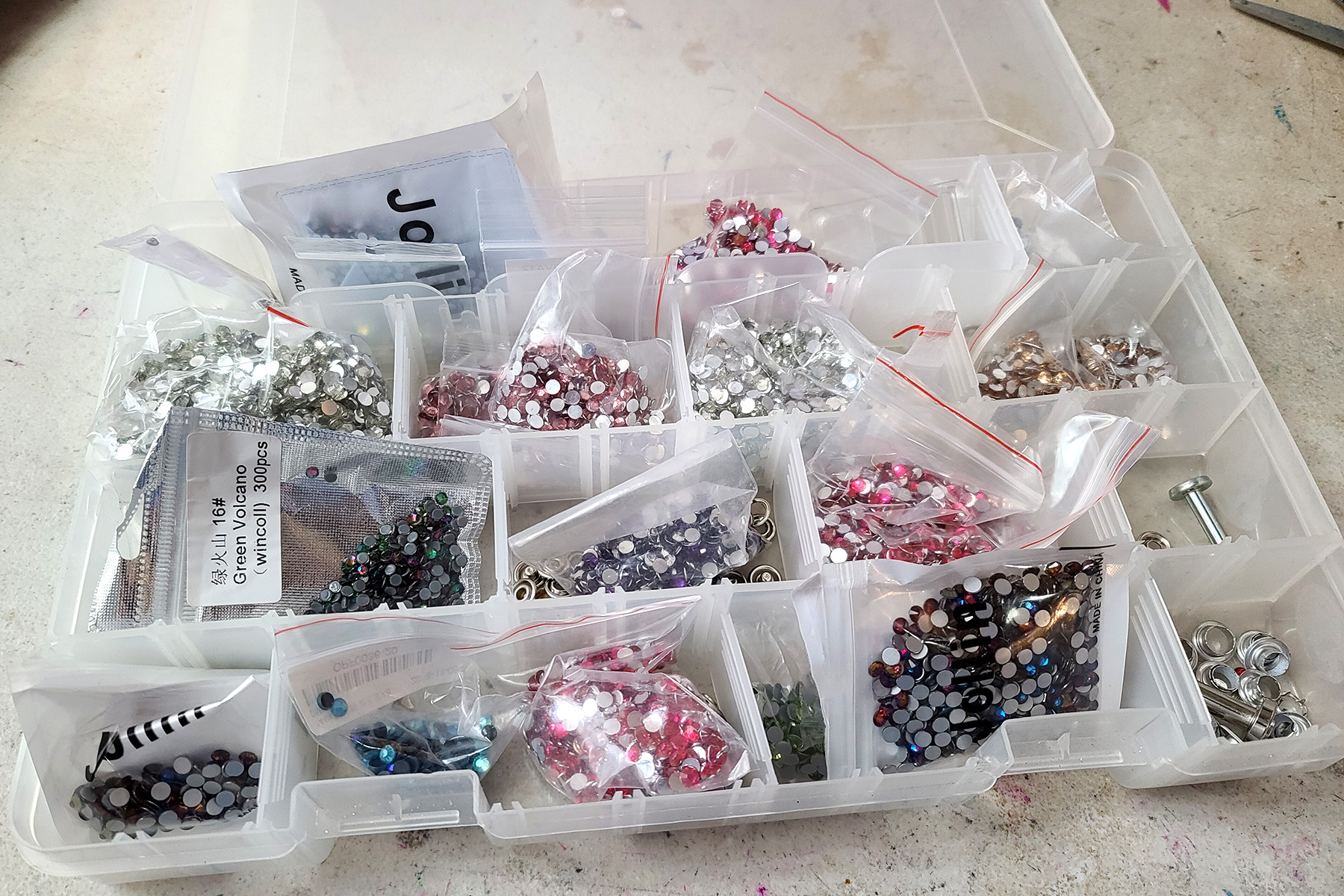 A white plastic tray-case filled with various colours of rhinestones.