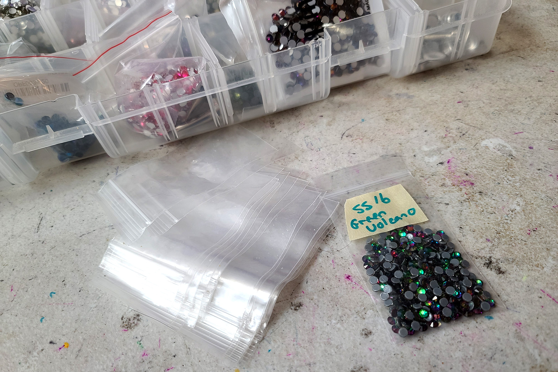 A small pile of clear zip top craft baggies, and one baggie filled with green rhinestones.
