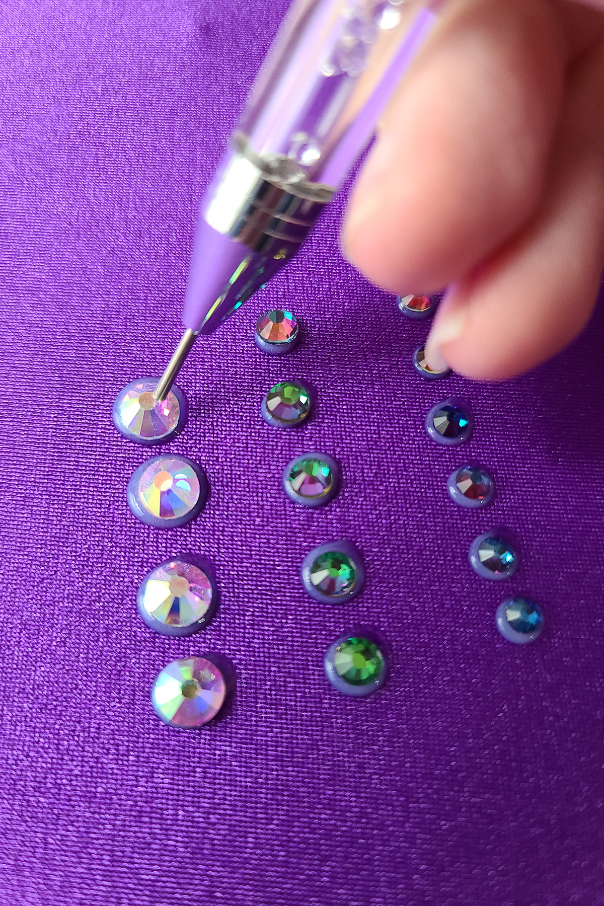 A close up view of the metal end of a wax picker being used to push crystals down into glue, on a purple fabric.