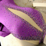 A purple skating dress on a dressform. Many crystals - in various colours - have been added to it.