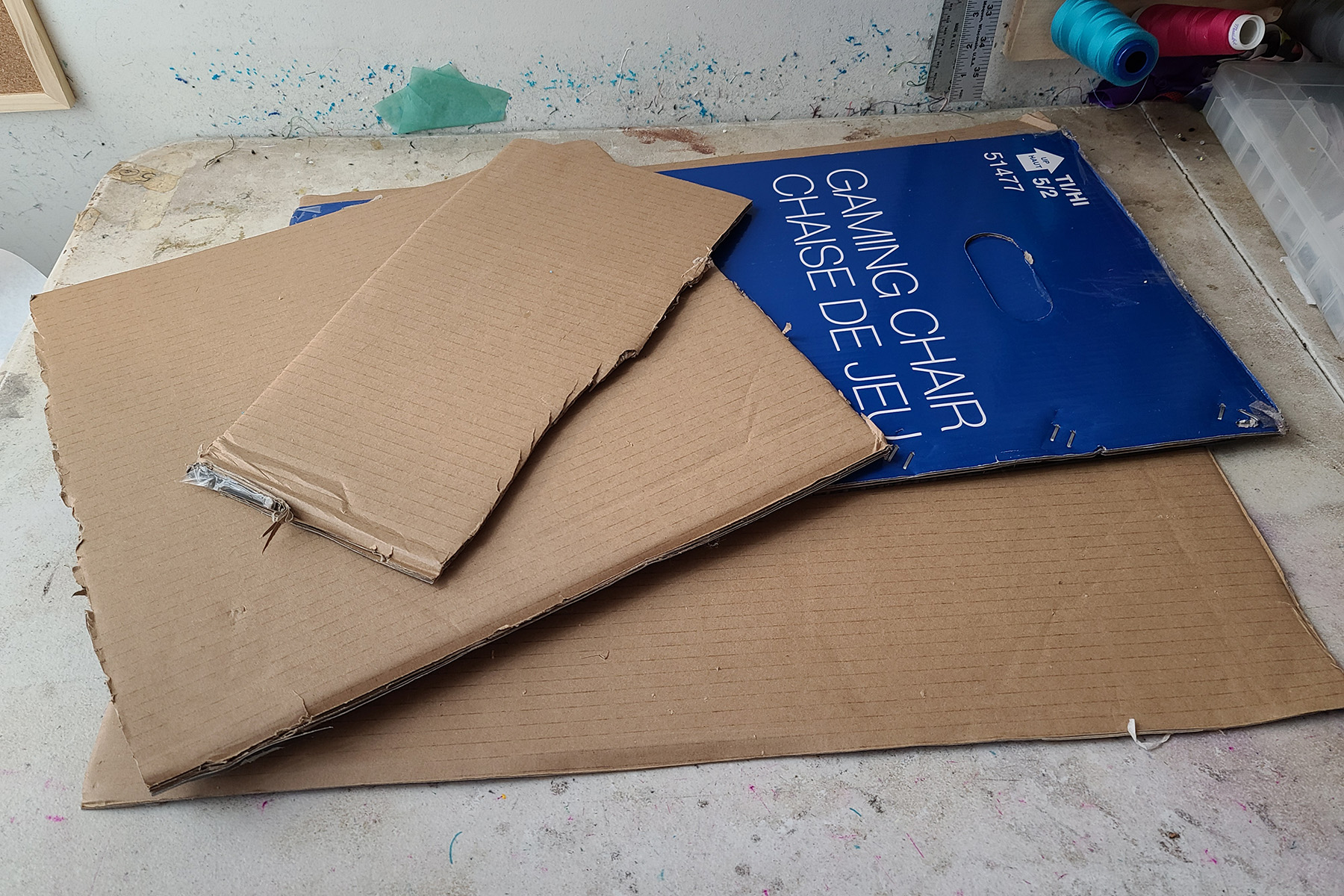 A small pile of large rectangles of thick cardboard. One piece is blue, and indicates it was an office chair box.