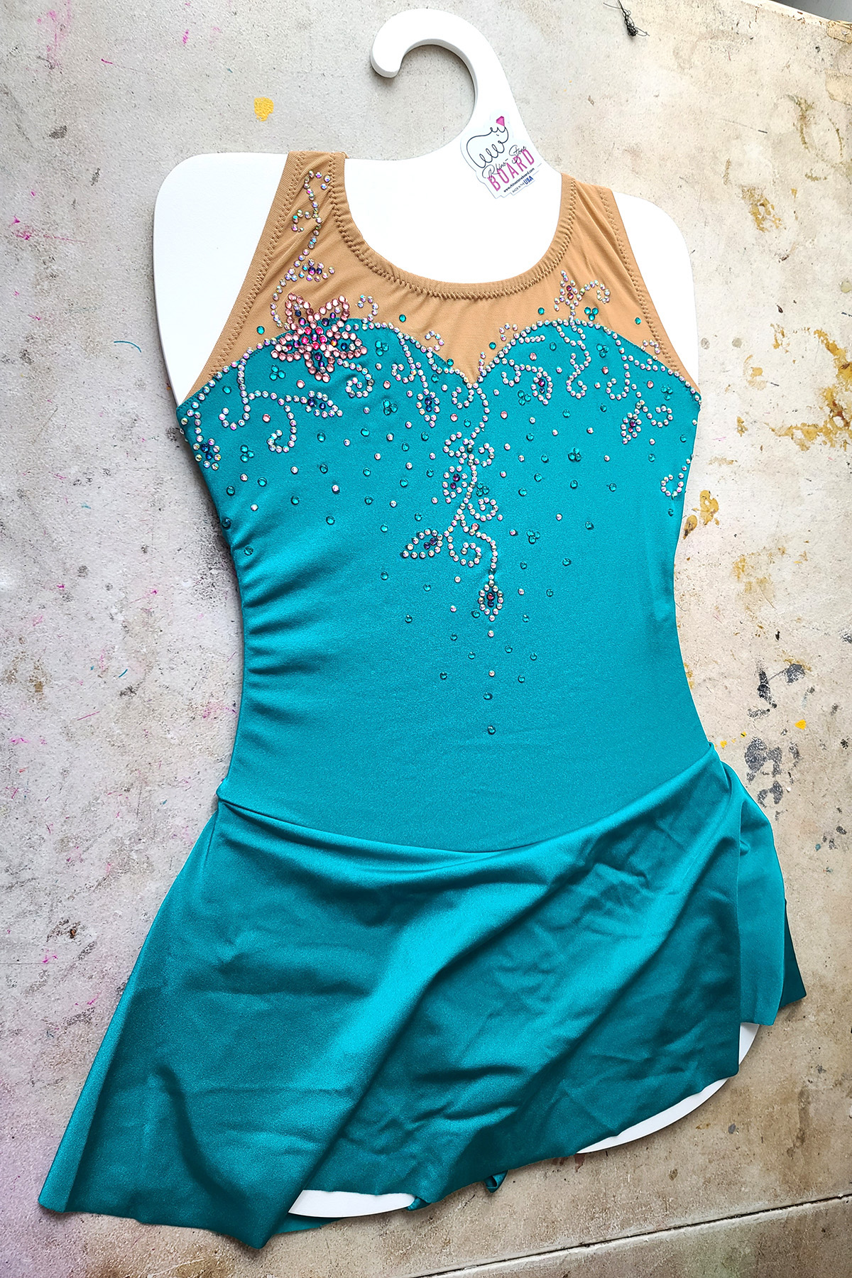 A light teal skating dress is on a white Rhino-Stone board.