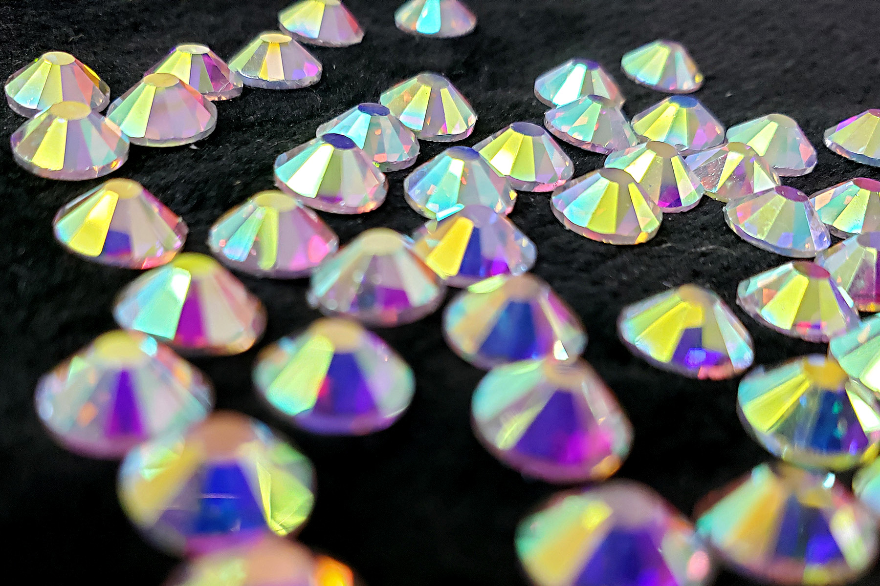A large pile of iridescent rhinestones against a black background.