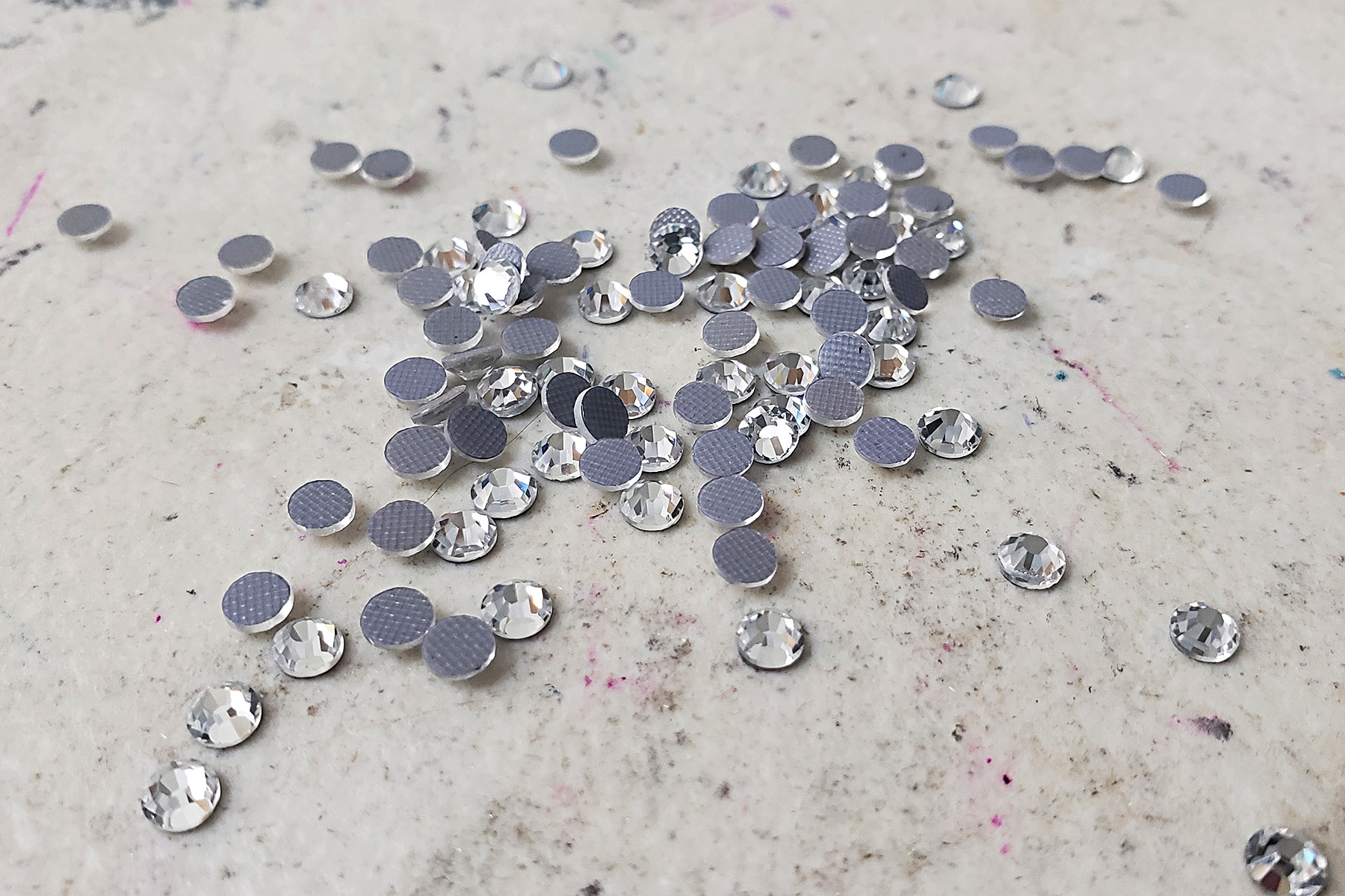 A pile of clear rhinestones on a grey work table.