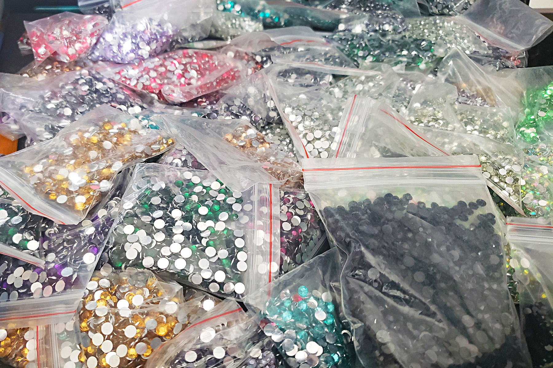 A close up view of a pile of bagged rhinestones in various colours.