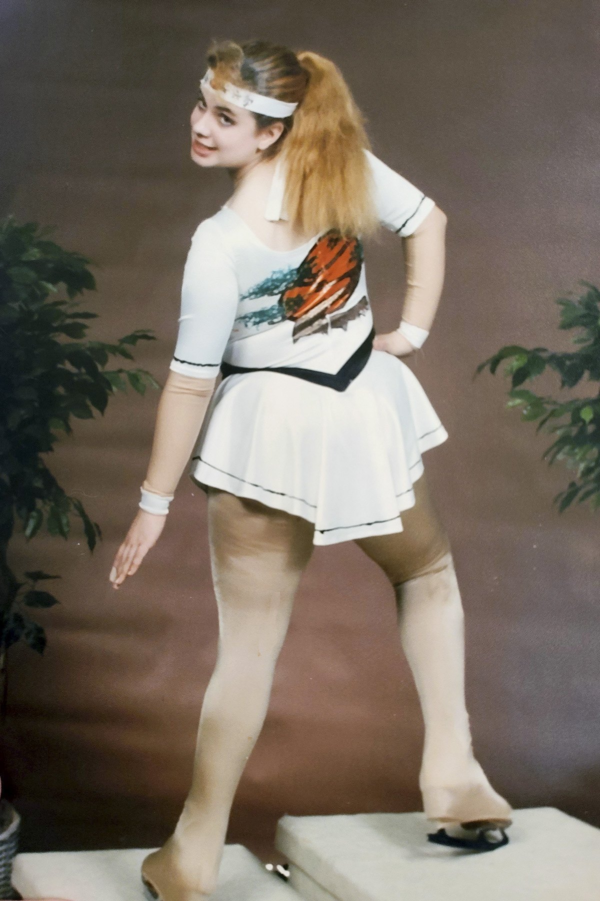 A figure skater on a podium. She has long strawberry blonde hair in a ponytail, and her back is to the camera.  She is wearing a white karate style skating dress.
