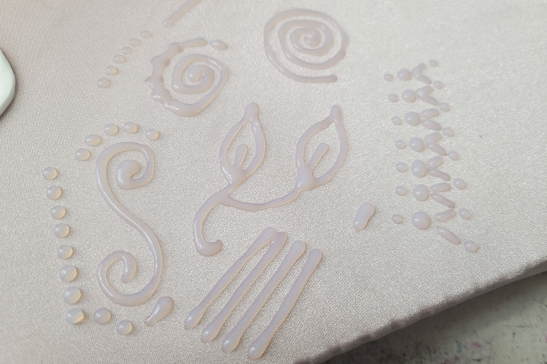 Clear designs piped onto pale pink spandex.