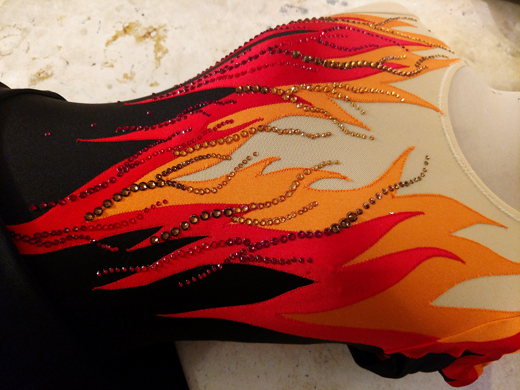 A close up view of the flames dress on a dress form, with red and orange crystals applied to it.