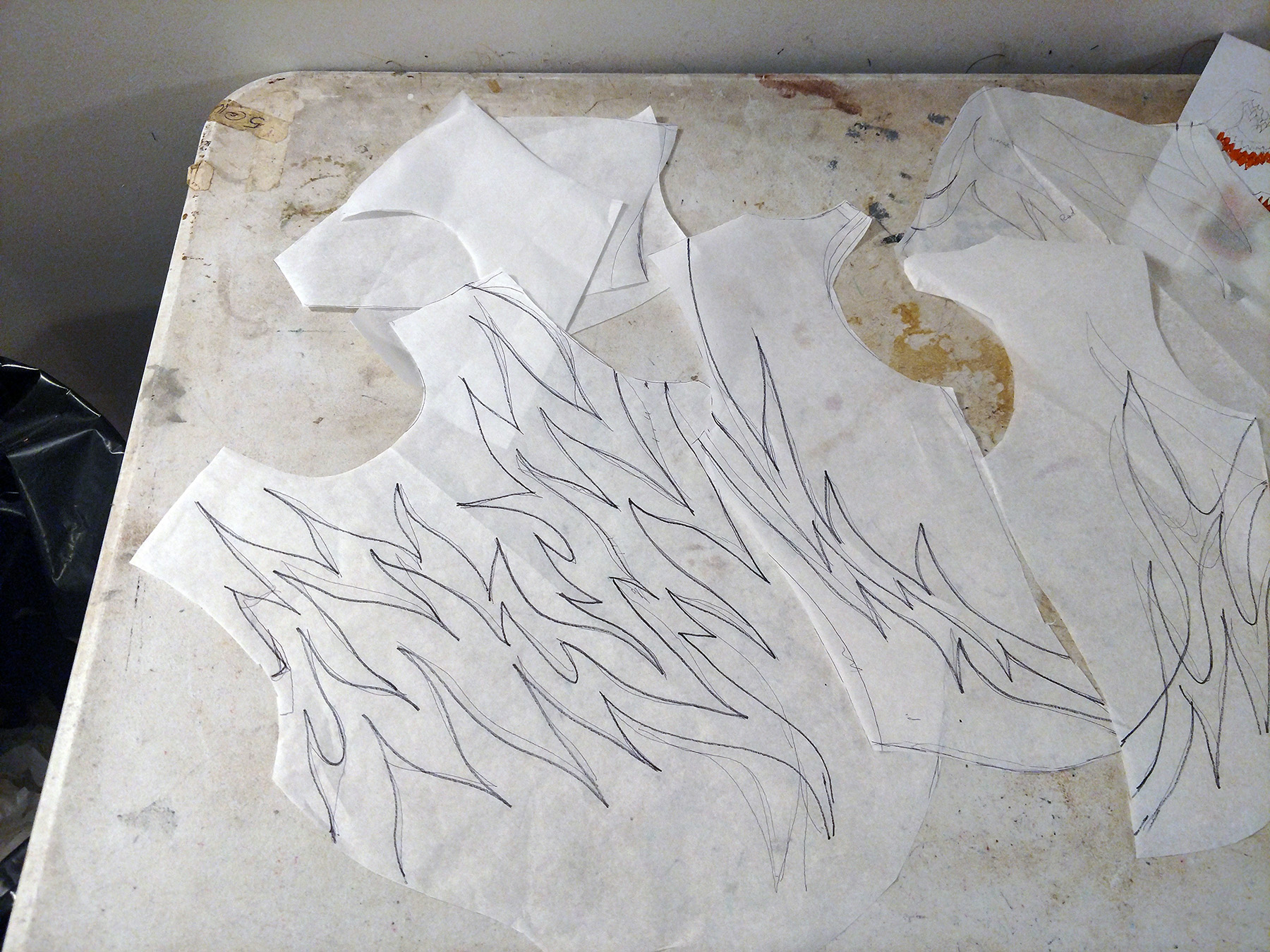 Several white paper pattern pieces on a work surface, all marked with a flames design.