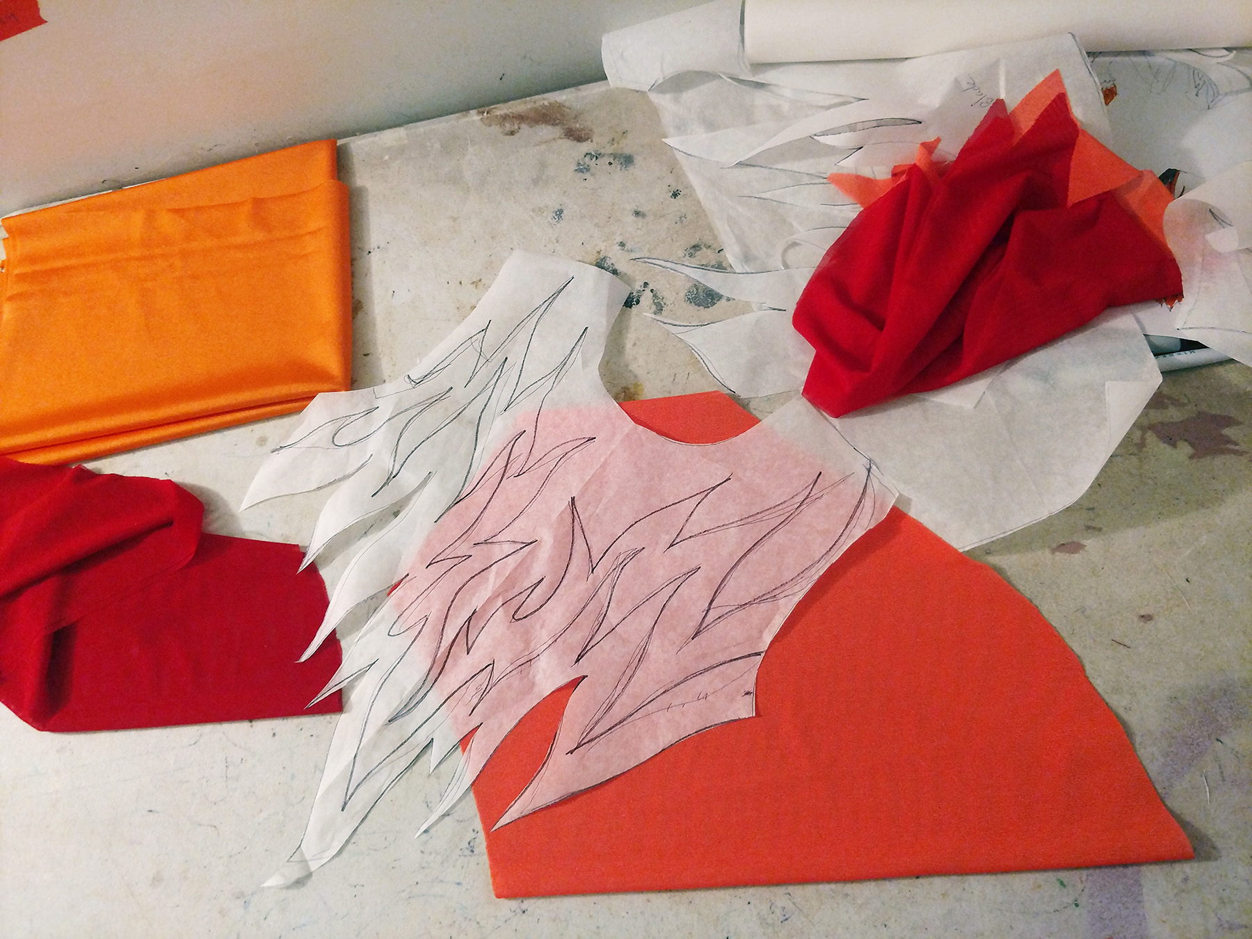 A pattern piece with a flames design is shown resting on top of some orange spandex.