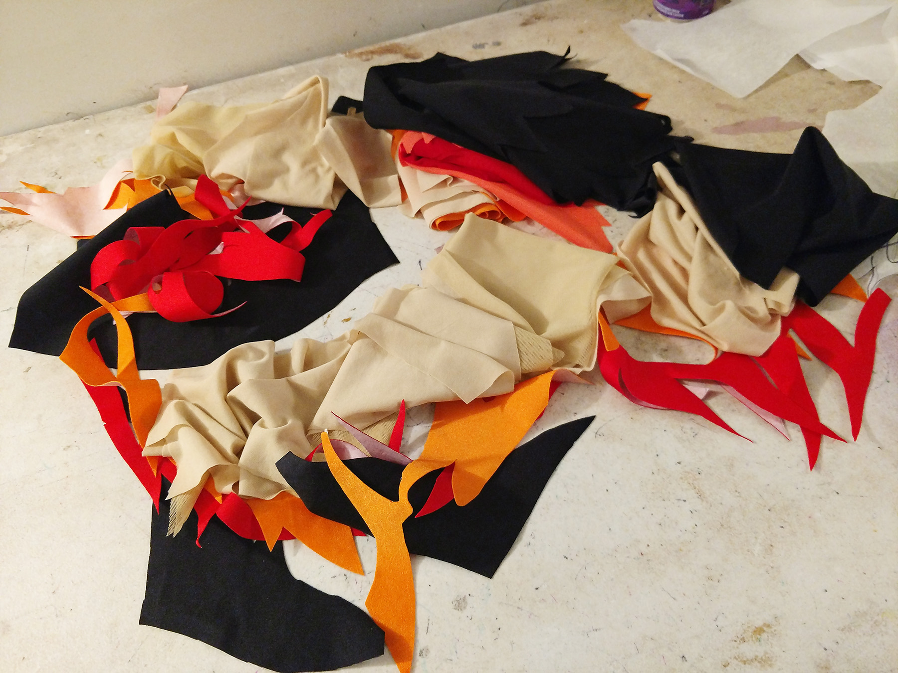 Piles of cut pieces of fabric - beige lining and mesh, red, black, and orange spandex, red and orange mesh.