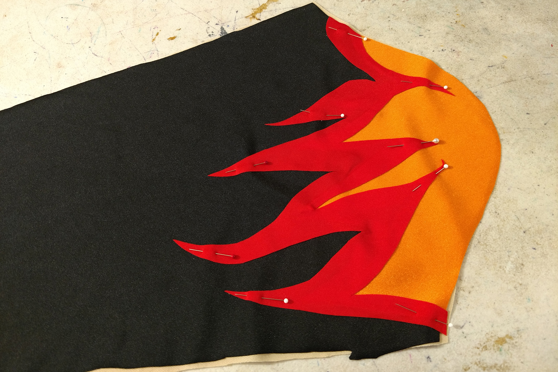 A black, red, and orange sleeve piece, pinned together.