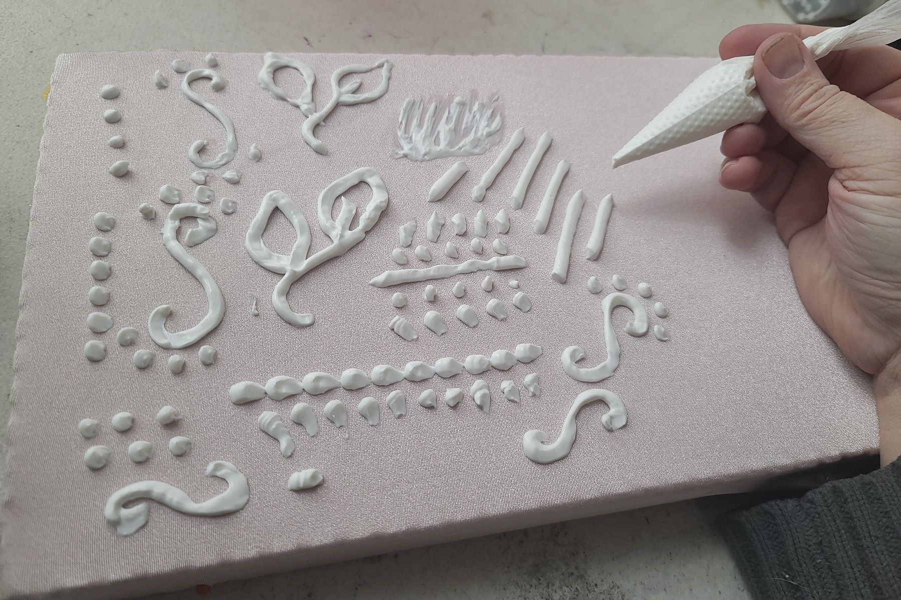 A pastry bag of caulking being used to pipe designs onto pale pink spandex.