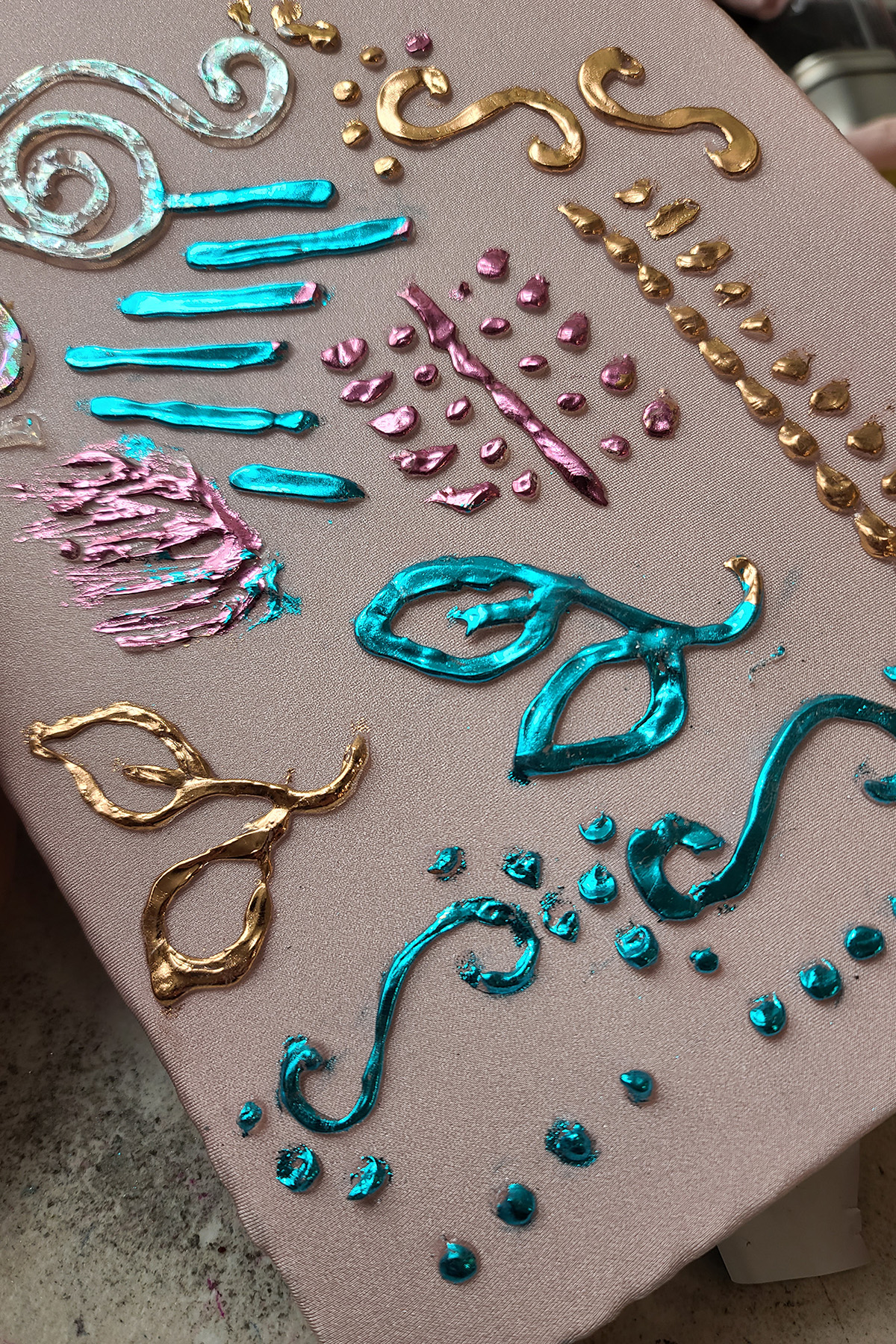 A piece of stretched pale pink spandex, covered with foil designs and doodles in copper, pink, and teal.