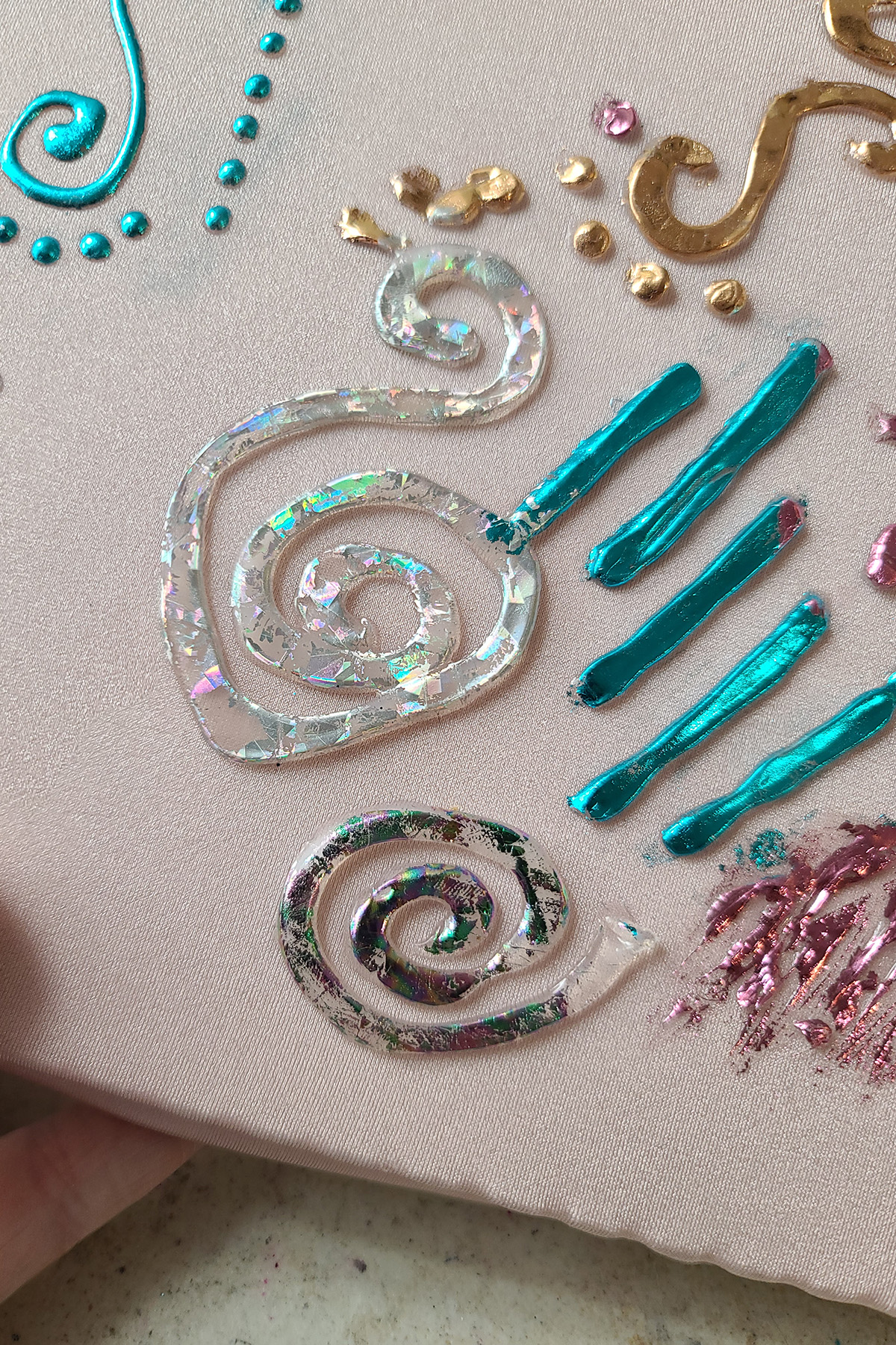 A close up view of a spiral design in caulking. It is partially covered with holographic silver foil.