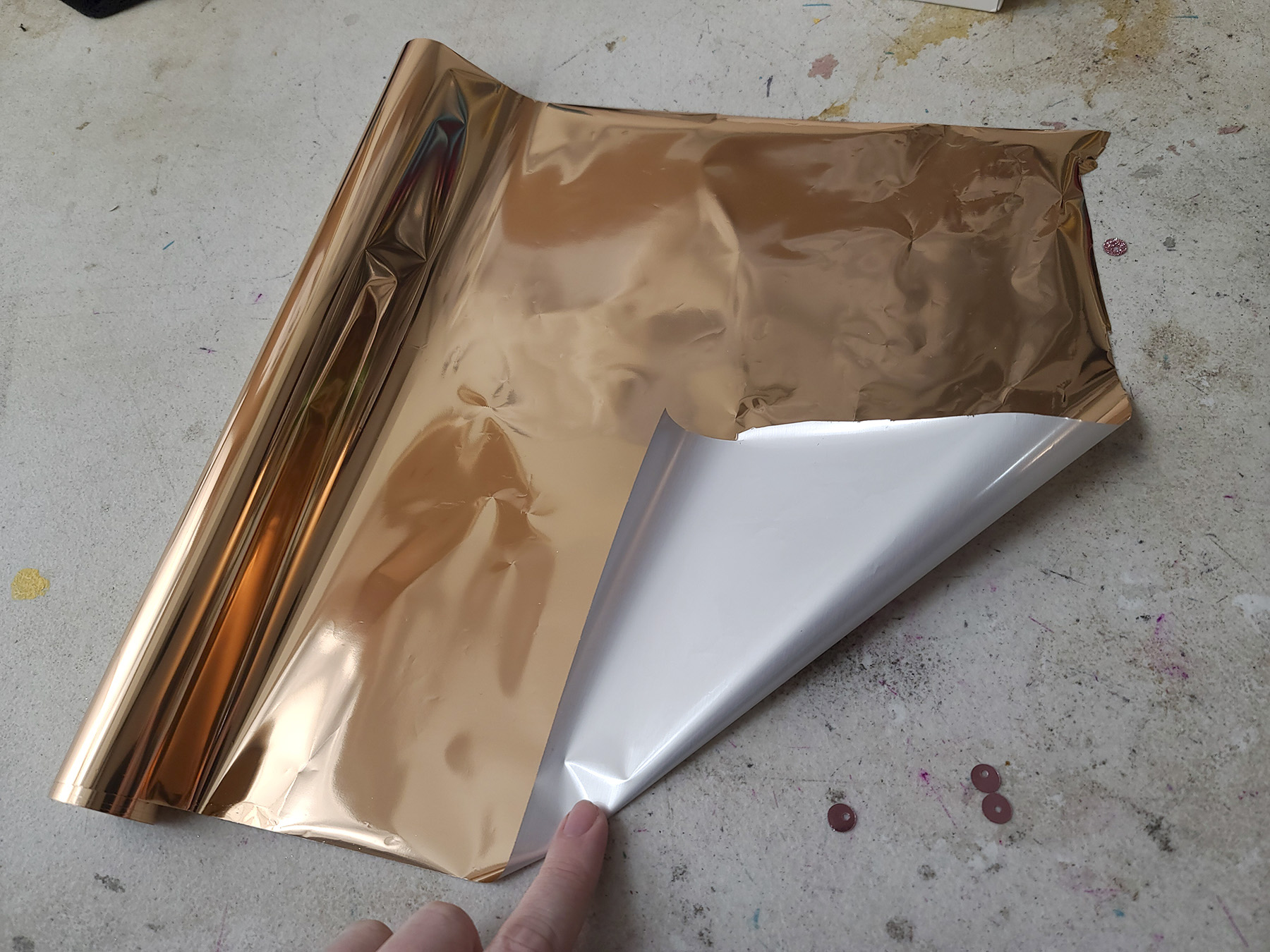 A roll of copper coloured foil paper. The corner is liften up, showing a white/silver underside.