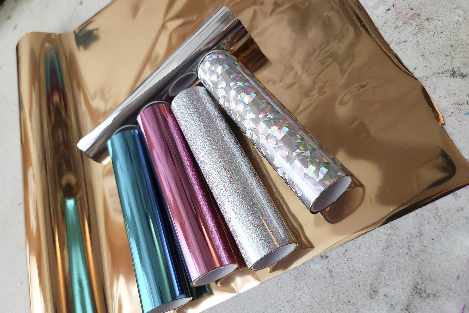 5 rolls of various colours of foil transfer paper laid out on a sheet of copper coloured foil.