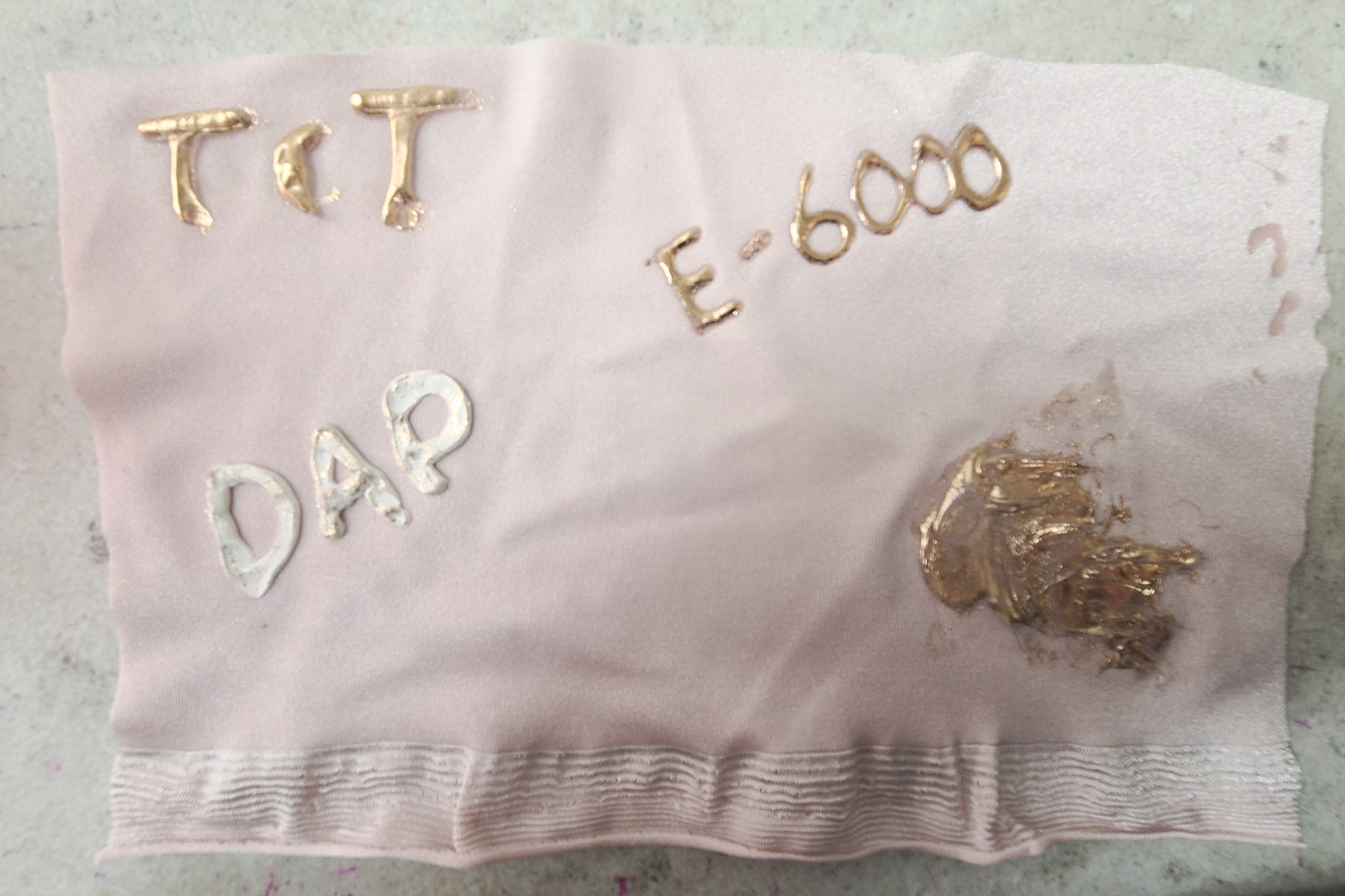 A piece of light pink spandex with sections of foil covered writing on it.