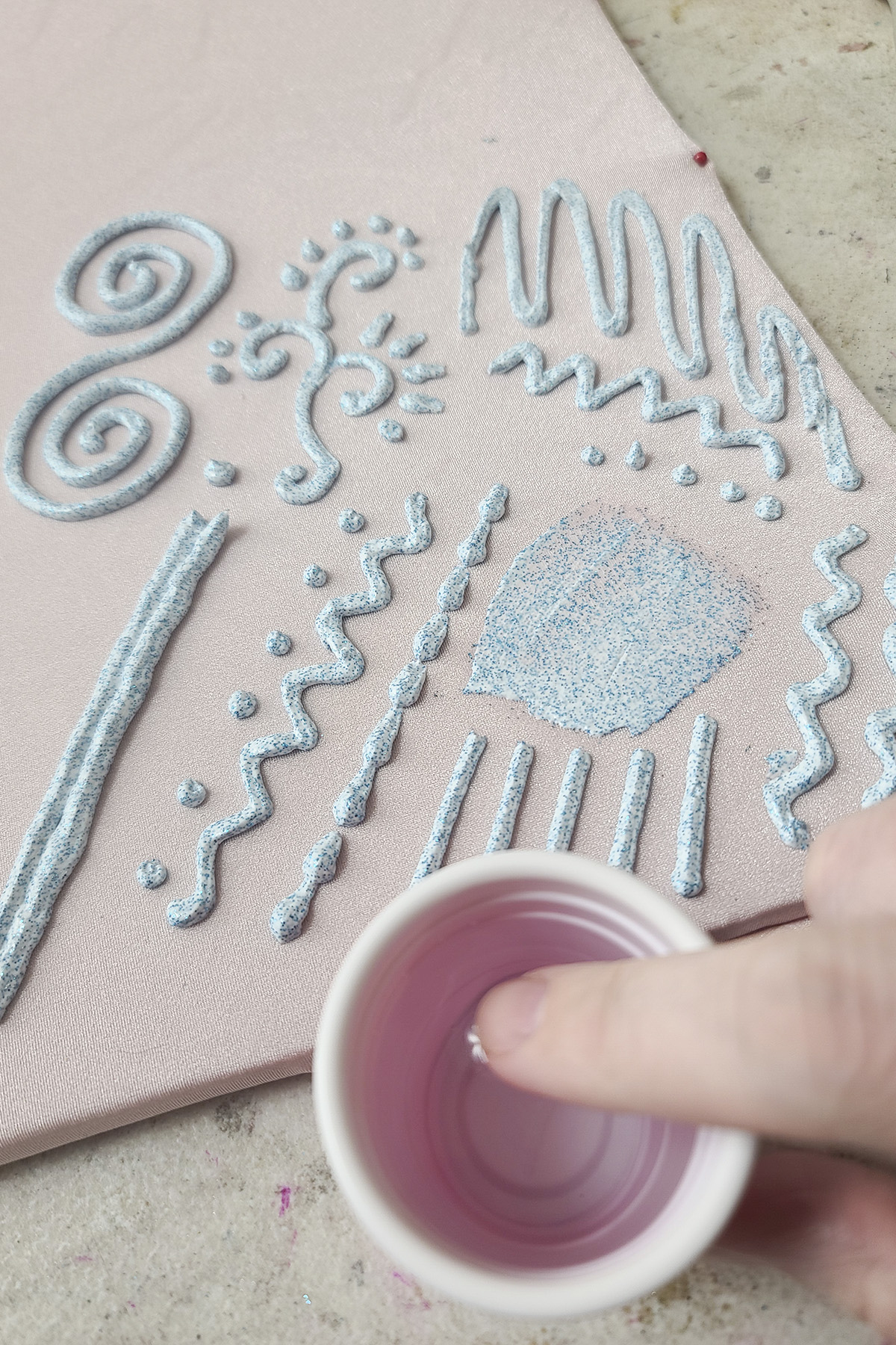 In front of a piece of stretched pink spandex with stretch glitter paint designs on it, a finger is being dipped into a small plastic cup of water.
