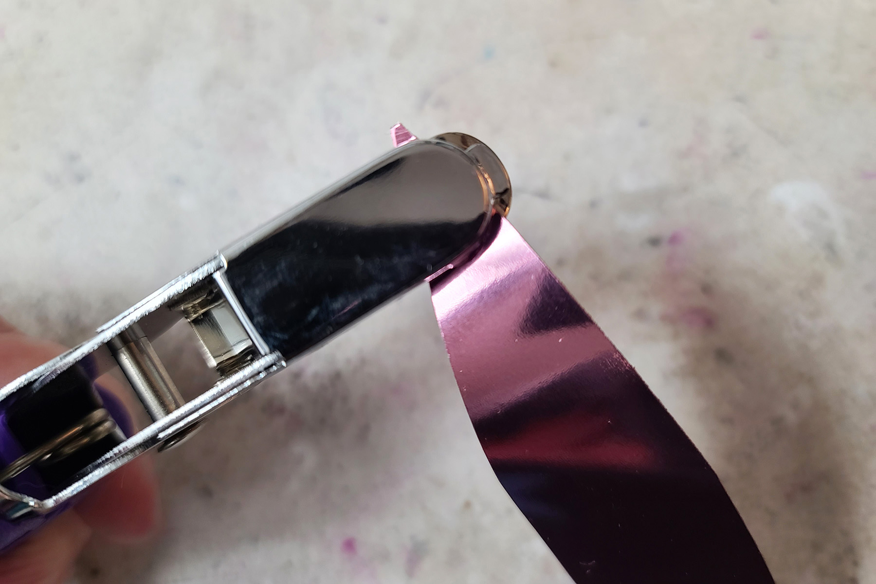 A hole punch is being used to create a small hole in one pointed end of a leaf shape sequin.